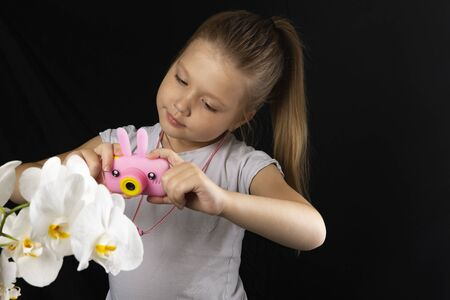 Little girl photographs a white orchid flower with a pink camera in the studio on a dark background