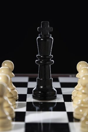 Black chess queen and army of white pawns on a chessboard on a black background