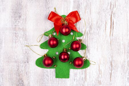 On a wooden table lies a felt Christmas tree made by hands with red balls and a red bow at the top. Christmas Craft