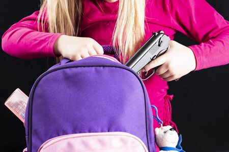 Girl hides a gun in a school backpack. Covert carrying weapons for protection. Weapons at school, assault at school, shooting.