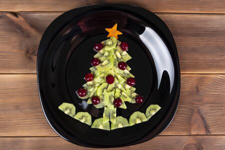 Kiwi fruit and berries Christmas tree on a black plate.