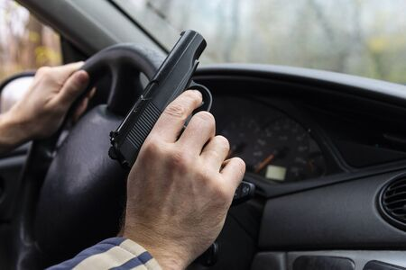 Man with a gun driving a car, male hand with a gun.