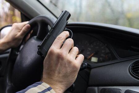 Man with a gun driving a car, male hand with a gun. 免版税图像 - 134966549