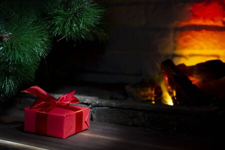 Christmas composition, gift under the tree near a burning fireplace, close-up. Stock Photo