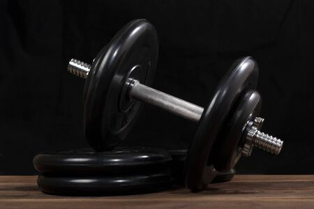 Big black male dumbbell on a brown wooden table on a black background Stock fotó