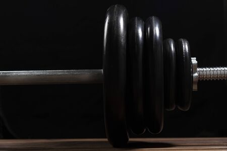 Big black barbell on a brown wooden table on a black background