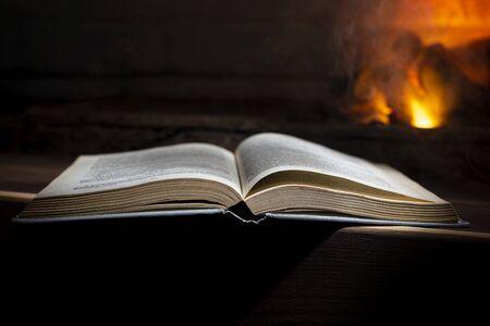 open book lies on a wooden near a burning fireplace