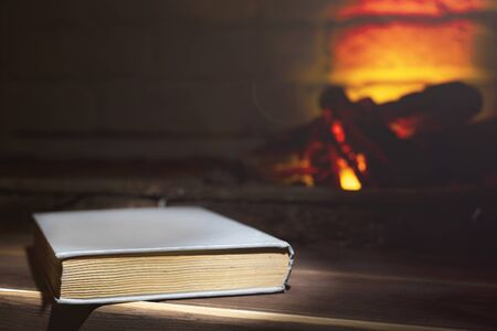 hardcover book lies on a wooden near a burning fireplace, close-up Stock Photo