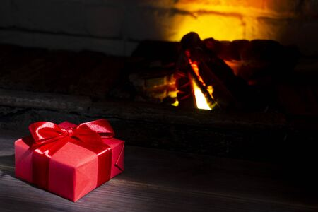 Christmas present near a burning fireplace on a wooden table, close-up Stock Photo