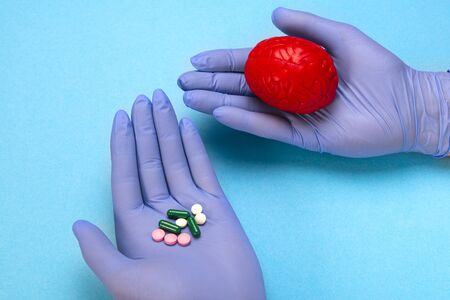 Red brain on a blue background with pills in the hands of a doctor. Some pills for the brain. This is symbolic for drugs, psychopharmaceuticals, nootropics and other drugs.