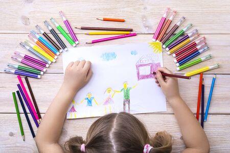 Ein Kind zeichnet mit seiner Familie eine Geburtstagskarte. Zeichnung von einem Kind mit bunten Filzstiften und Bleistiften. Glückliche Familie. Kinderzeichnung Standard-Bild