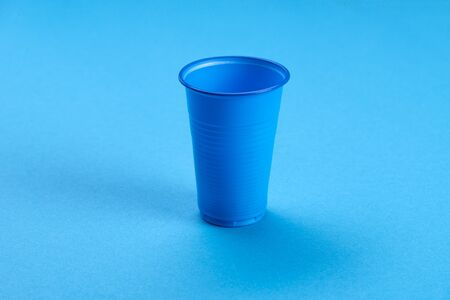 Blue empty plastic cup on a blue background. Recycling plastic. Plastic waste. Ecological concept. Фото со стока