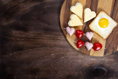 Cooking, sandwiches, heart-shaped snacks, top view. Heart-shaped sausages, and sandwiches with cherry tomatoes with croutons on a wooden tray. Valentines Day