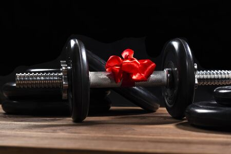 Black dumbbell with a red bow for a gift on a wooden table near sports equipment. A gift to the athlete. Healthy lifestyle, sport.