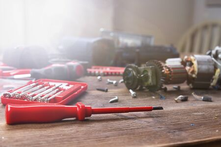 Details of electrical appliance and repair tools on a wooden table in a repair shop Stok Fotoğraf