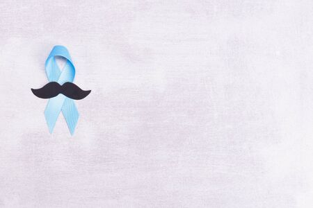 Healthcare and medicine concept - blue prostate cancer awareness ribbon and paper black mustache, achalasia and adrenocortical cancer, on gray background, flat lay, top view, place for text