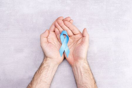 Healthcare and medicine concept - blue ribbon of prostate cancer awareness in male hands, achalasia and adrenocortical cancer, on gray background, flat lay, place for text Stok Fotoğraf