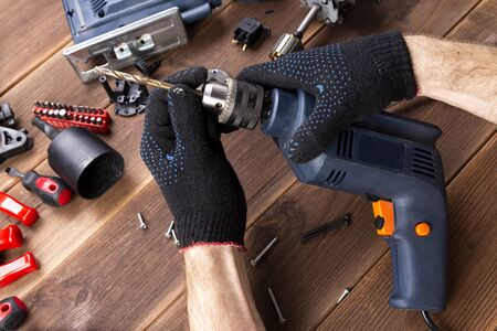 the master repairs a broken electrical device: drill, cutter on a wooden table. Electric Tool Repair Shop Stok Fotoğraf