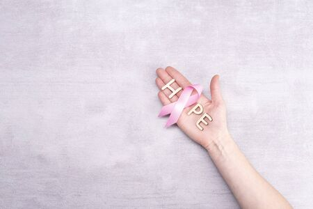 healthcare and medicine concept - female hands holding pink breast cancer awareness ribbon and letters of the word HOPE on gray background