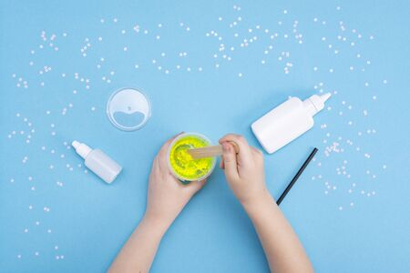 How to make mucus at home. Childrens art project. DIY concept. Childrens hands making slime toy on blue. Step by step photo instruction Stok Fotoğraf