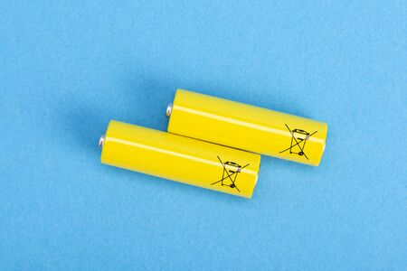 Two yellow batteries on a blue background, top view.