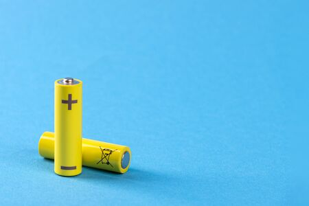 Two yellow batteries on a blue background with place for text.
