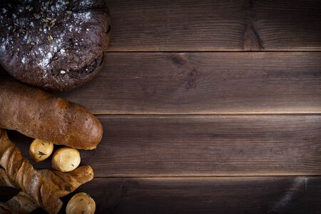 Varied handmade bread on a wooden table with copy space, top view, flat lay.