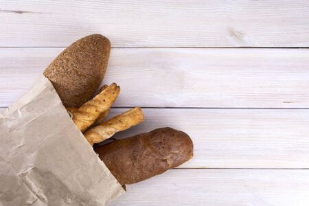Bread in a paper bag on a light wooden background, top view. Stok Fotoğraf