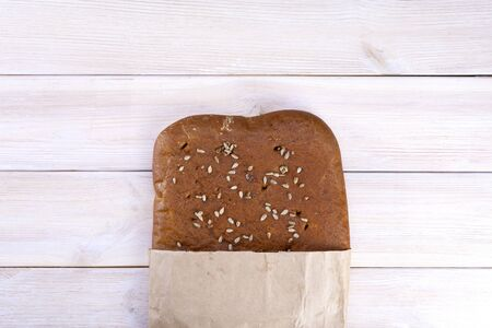Ciabatta bread with seeds in a paper bag on a light rustic background.