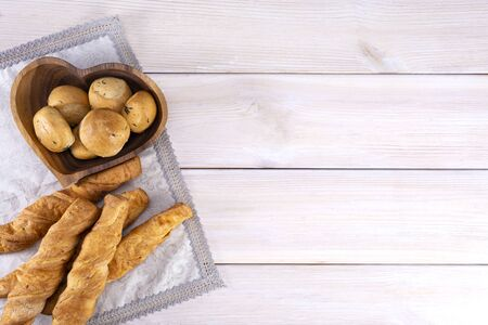 Homemade freshly baked breadsticks with cheese and garlic buns on a light wooden background, with place for text, top view.