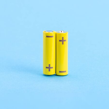 Two yellow batteries on a blue background. Stockfoto