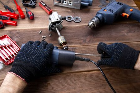 the master repairs a broken electrical device: drill, cutter on a wooden table. Electric Tool Repair Shop.