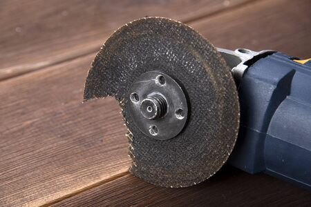 A grinder with a broken blade on a wooden table. The danger of using power tools. Stok Fotoğraf