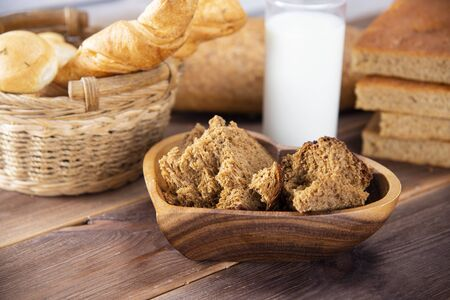 Broken bread in pieces in a wooden plate and other types of bakery products with a glass of milk on a dark table. Stok Fotoğraf