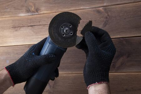 Grinder with a broken blade in the hands of working gloves on a wooden table. Danger of using a power tool. Stockfoto