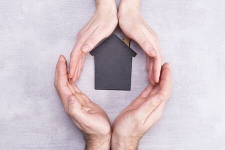 Hands of man and woman surround a model of a dark house on a gray background. Real estate and insurance concept, flat lay, top view Stok Fotoğraf