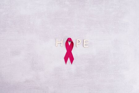 healthcare and medicine concept - red breast cancer awareness ribbon and letters of the word HOPE on a gray background with place for text Stok Fotoğraf