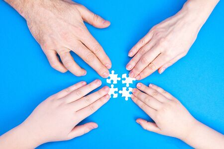 Hands of man, woman and children collect puzzle on a blue background background. Conceptual image of joint cooperation in the family. View from above