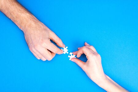 Hands of man and woman collect puzzles on a blue background background. Conceptual image of joint cooperation in the family. View from above Stok Fotoğraf