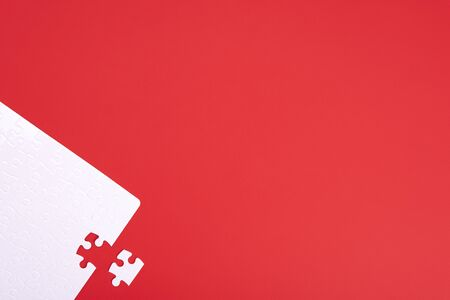 A puzzle of white pieces with one seized element on a red background with place for your text.