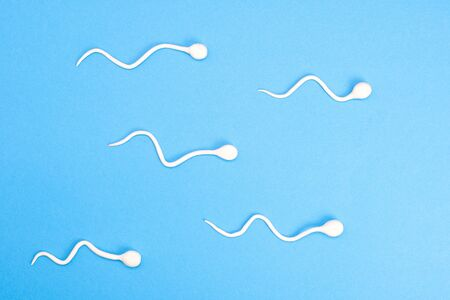 Active sperm swim on a blue background. The concept of pregnancy, fertilization of the egg. Top view