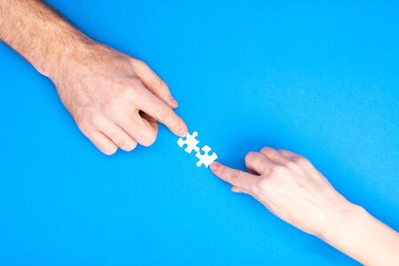 Hands of man and woman collect puzzles on a blue background background. Conceptual image of joint cooperation in the family. View from above.