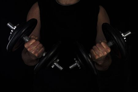 hand of a man with big biceps holds a steel type-setting dumbbell, low key, sports training with weight. 版權商用圖片