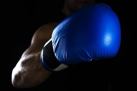 Men's hand in a blue boxing glove on a black background makes a punch.