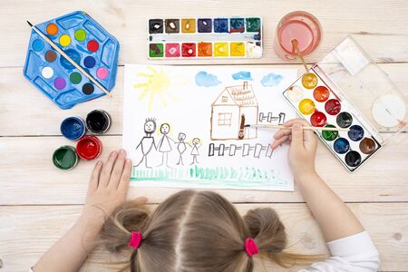 A child draws a birthday card with his family. The drawing was made by a child using color paints. A happy family. Childrens drawing. View from above Banque d'images