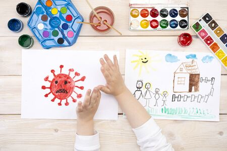 A child draws a coronovirus and his family on a piece of paper. Coronovirus and family at home. The drawing was made by a child using color paints. Childrens drawing. View from above Banque d'images
