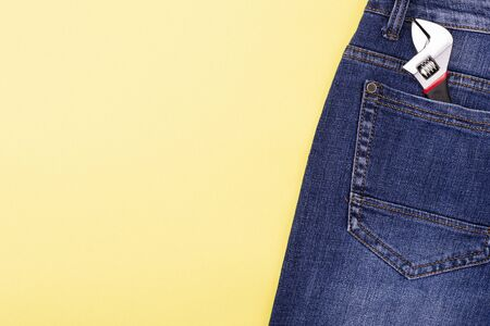 Wrenches in a craftsman jeans pocket on a yellow background with place for text. Reklamní fotografie