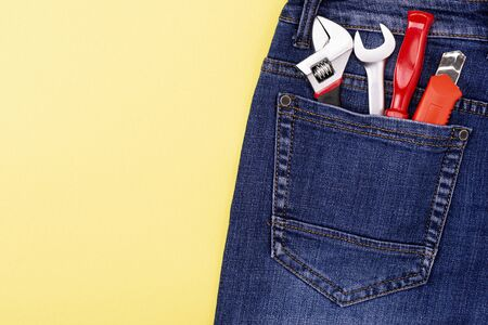 tools in the pocket of a craftsman jeans on a yellow background with place for text Reklamní fotografie