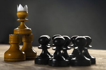 Small courageous pawn with an artificial paper crown suit, leading others into battle with the enemy - business entrepreneur leadership concept. Black lives matter