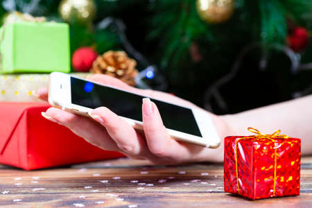 People hand using smartphone for shopping on winter holidays blur Christmas tree background
